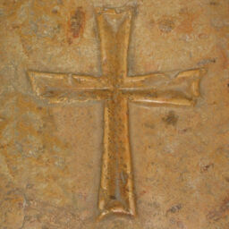 A simple cross engraved in brown toned stone.